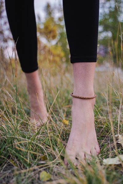 Model wearing tan leather anklet, jewelry made in Victoria B.C. by Woven Stone Co