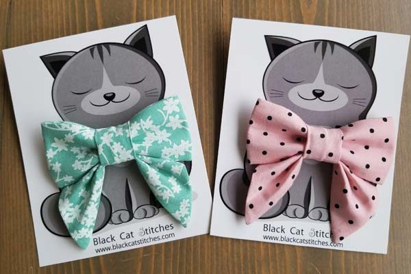 Cat bowties, one with flowers and one with polka dots by Black Cat Stitches
