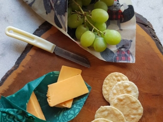 beeswax wraps folded around cheese and grapes, alternative to saran wrap, made by Coastal Hive