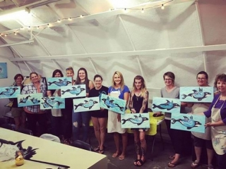 group of woman holding paintings at Vancouver Island paint night in Courtenay