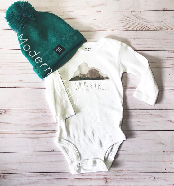 """Parksville screenprint onesie with mountains saying """"Wild and Free"""", by Modern Mini's"""