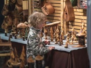 boy admiring wood carvings at VIM, Vancouver Island craft market