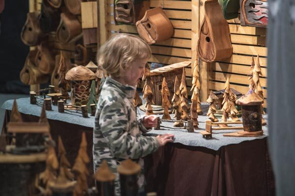boy admiring wood carvings at VIM, Vancouver Island craft market